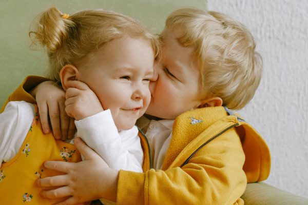 cheerful-little-siblings-hugging-in-armchair-at-home-3771605-sm