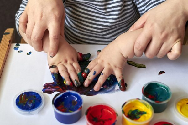 Mom teaches a child to draw with finger paints, the early development of the child.